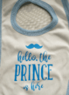 White baby bib ( The prince is here logo )